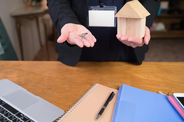 家の模型と鍵を持つ男性