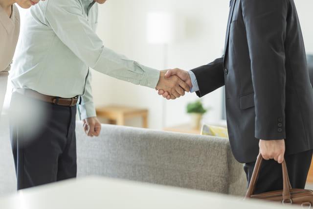 握手するビジネスマンとシニア夫婦