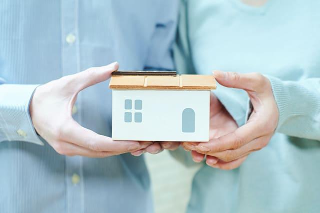 家の模型を持つ夫婦