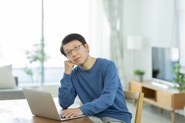 パソコンの前で考える男性