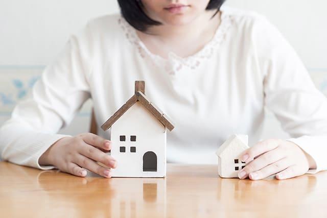 女性と2つの家の模型